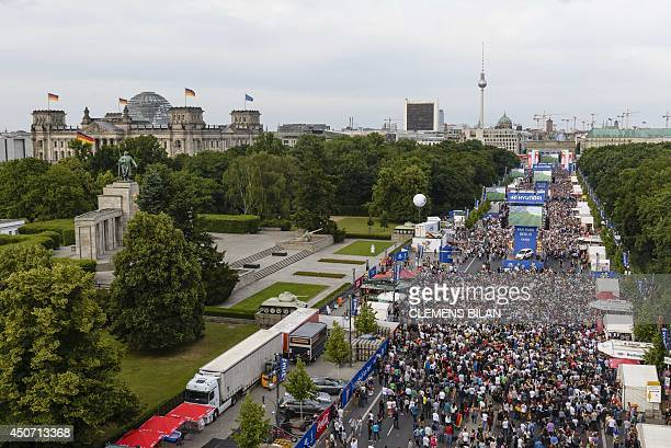 A general view shows Germany fans pictured near the Brandenburg Gate and the Reichstag building in Berlin on June 16 2014 during the public viewing...