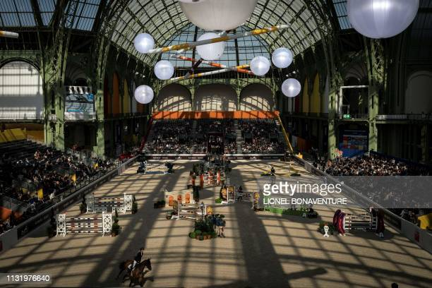 A general view shows horseriders taking part in 'Le Saut Hermes' horse jumping show under the glass canopy of the Grand Palais in Paris on March 22...
