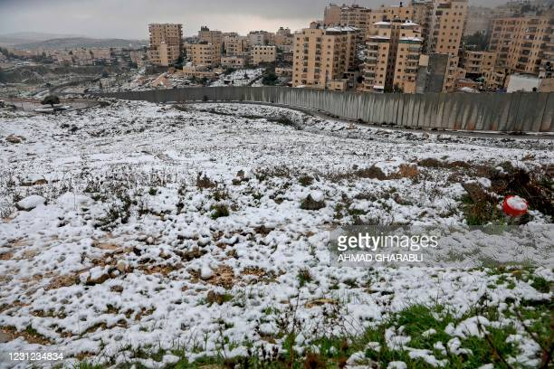 General view shows Israel's controversial separation wall and the Palestinian Shuafat refugee camp following heavy snowfall in the Israeli-annexed...