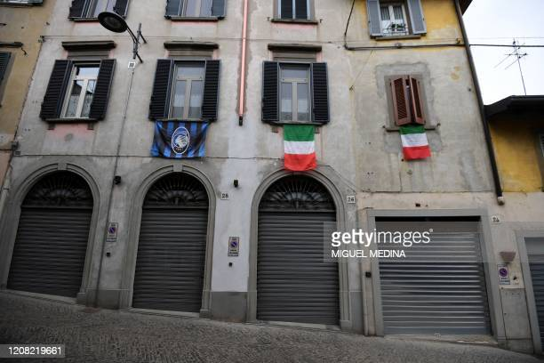 A general view shows Italian flags and an Atalanta Bergamo football team flag hanging over closed shops in a deserted street of Albino near Bergamo...