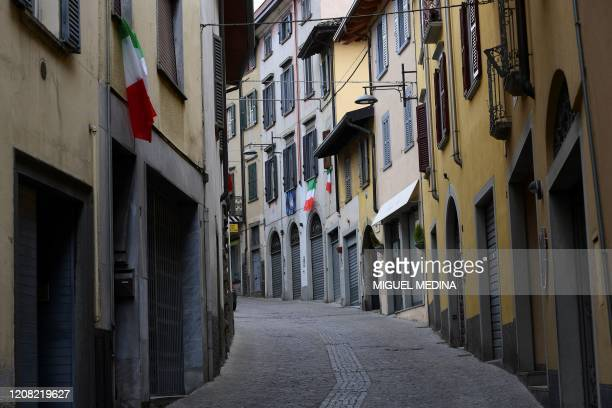 General view shows Italian flags hanging from windows in a deserted street of Albino near Bergamo, Lombardy, on March 25 during the country's...