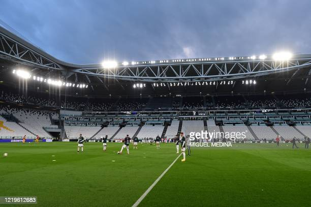 General view shows Juventus players warm up in an empty stadium prior to the Italian Cup semi-final second leg football match Juventus vs AC Milan on...