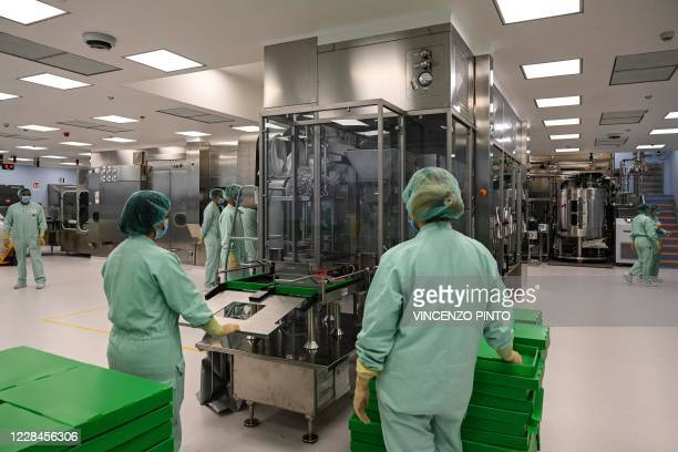 General view shows laboratory technicians take part in filling and packaging tests for the large-scale production and supply of the University of...