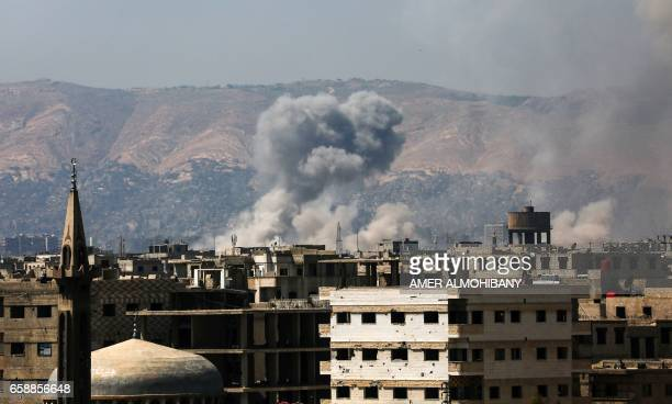A general view shows moke rising from buildings following an air strike on Jobar a rebelheld district on the eastern outskirts of the Syrian capital...