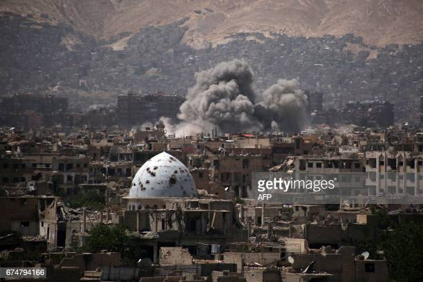 TOPSHOT A general view shows moke rising from buildings following an air strike on Jobar a rebelheld district on the eastern outskirts of the Syrian...