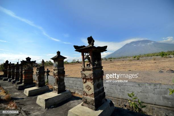 A general view shows Mount Agung behind Balinese Hindu temples seen from Karangasem on the Indonesian resort island of Bali on September 23 2017...