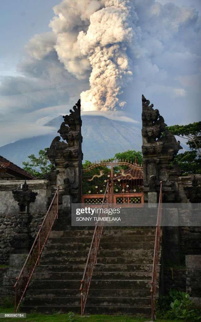 A general view shows Mount Agung erupting betwen Balinese a temple seen at night from Kubu sub-district in Karangasem Regency on Indonesia's resort island of Bali on November 28, 2017. Indonesian authorities extended the closure of the international airport on the resort island of Bali for a second day over fears of a volcanic eruption. /