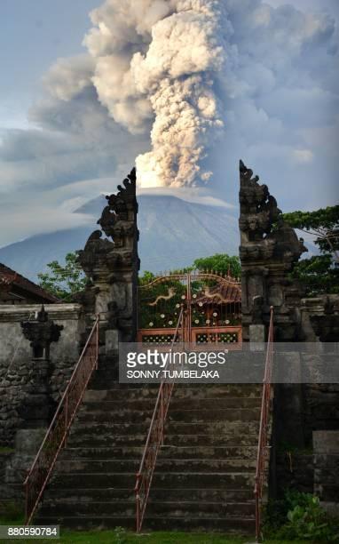 A general view shows Mount Agung erupting betwen Balinese a temple seen at night from Kubu subdistrict in Karangasem Regency on Indonesia's resort...