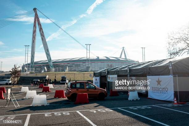 General view shows on January 12, 2021 a car lining up to go through a drive-in swab testing centre for COVID-19 set up by the Italian Army on the...