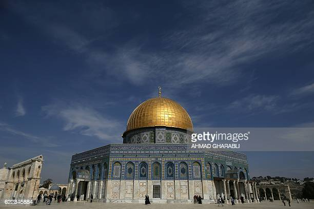 A general view shows Palestinians walking past the Dome of Rock at the AlAqsa Mosque compound after the Friday prayer in Jerusalem's Old City on...