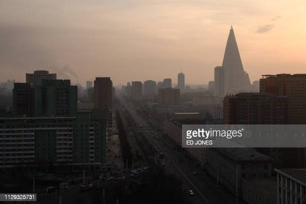 A general view shows pedestrian and traffic amid the Pyongyang city skyline and Ryugyong hotel on March 9 2019 North Korea will hold its 14th Supreme...