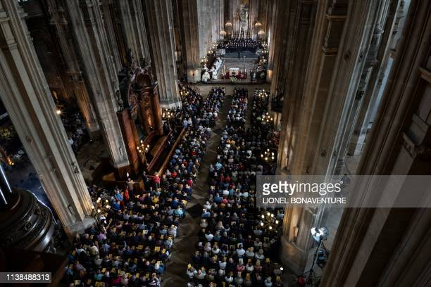 A general view shows people attending Mass in tribute to the NotreDame de Paris Cathedral at the Saint Eustache church in Paris on Easter Sunday on...