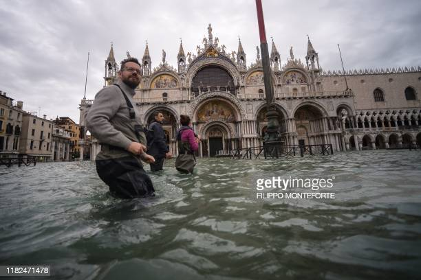 TOPSHOT A general view shows people walking across the flooded St Mark's Square by St Mark's Basilica on November 15 2019 in Venice two days after...