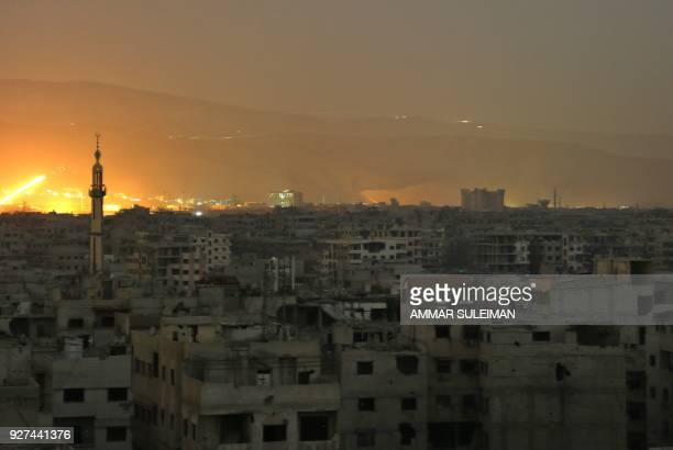 TOPSHOT A general view shows smoke and flames rising from buildings following a reported Syrian government missile attack on the rebelheld town of...