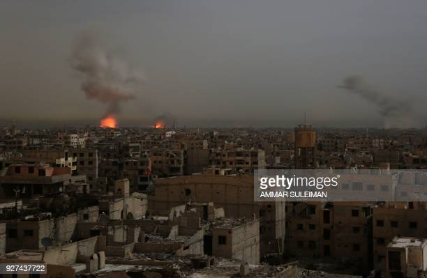 TOPSHOT A general view shows smoke and flames rising from buildings following reported Syrian government air strikes on rebelheld town of Saqba in...