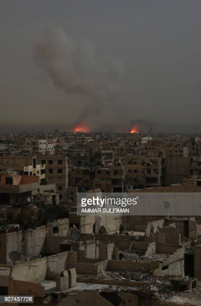 A general view shows smoke and flames rising from buildings following reported Syrian government air strikes on rebelheld town of Saqba in the...
