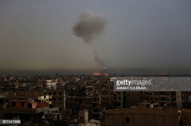 A general view shows smoke and flames rising from buildings following reported Syrian government bombardments on rebelheld town of Hamouria in the...
