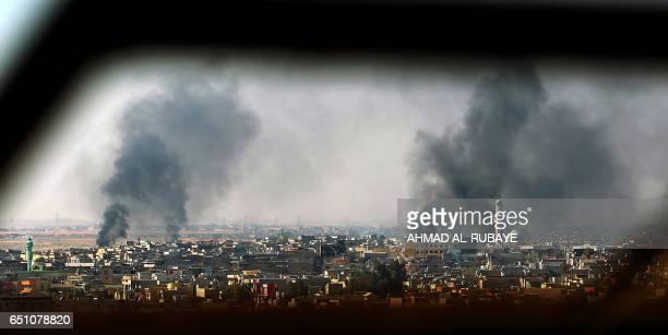 TOPSHOT A general view shows smoke billowing from AlAmil neighborhood in Mosul on March 10 as Iraqi forces shell enemy positions during an offensive...