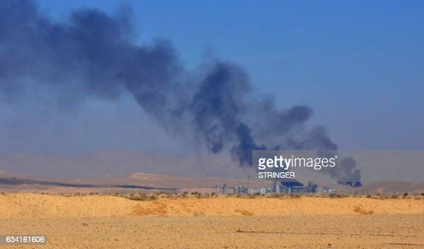 A general view shows smoke billowing from an oil field as Syrian government forces advance towards the strategic Jihar oil fields on the eastern...