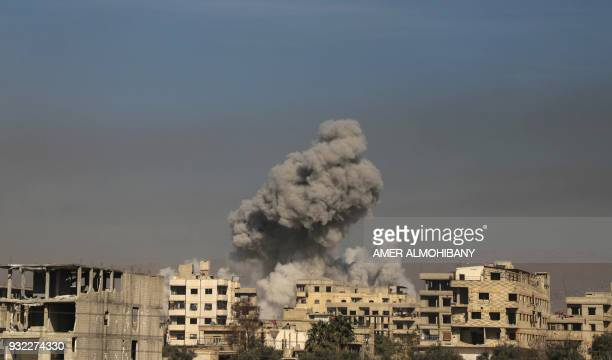 TOPSHOT A general view shows smoke billowing in Hazeh in the rebel enclave of Eastern Ghouta on the outskirts of Damascus on March 15 2018 during...