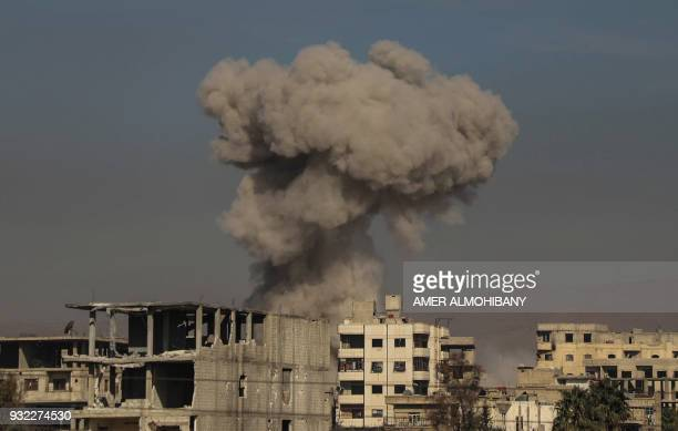 A general view shows smoke billowing in Hazeh in the rebel enclave of Eastern Ghouta on the outskirts of Damascus on March 15 2018 during reported...