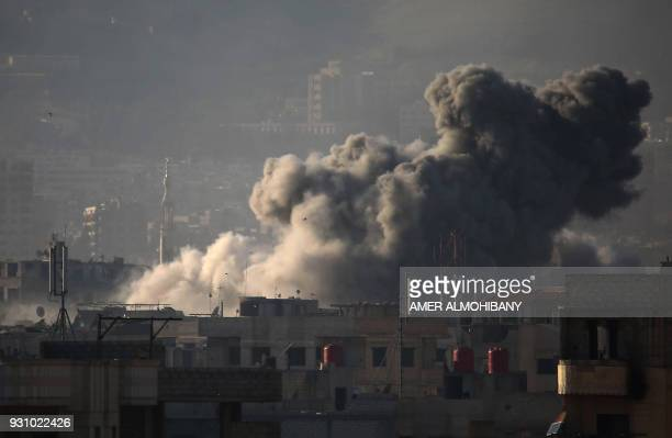 A general view shows smoke billowing in Zamalka in the rebel enclave of Eastern Ghouta on the outskirts of Damascus on March 12 2018 during reported...