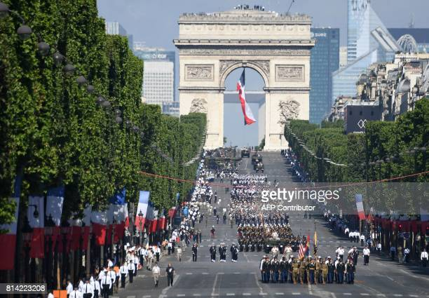 A general view shows soldiers dressed as World War I Sammies carrying the US flag as they lead US troops marching during the annual Bastille Day...