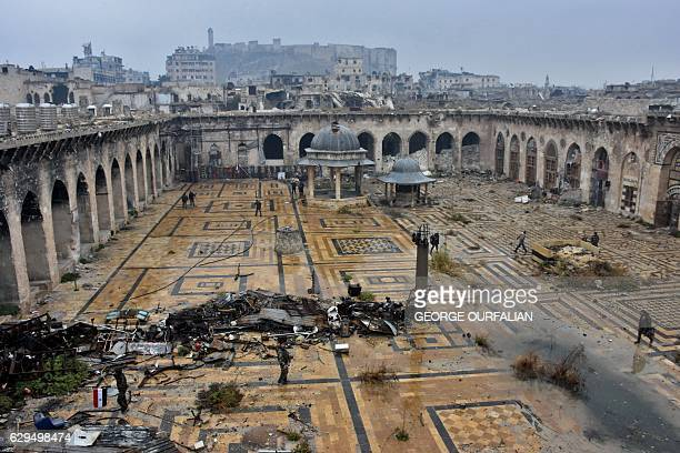 A general view shows Syrian progovernment forces walking in the ancient Umayyad mosque in the old city of Aleppo in the foreground and the city's...