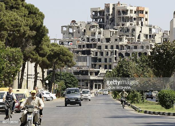 A general view shows Syrians driving down the street in front of a damaged building in a governmentheld area of the central Syrian city of Homs on...