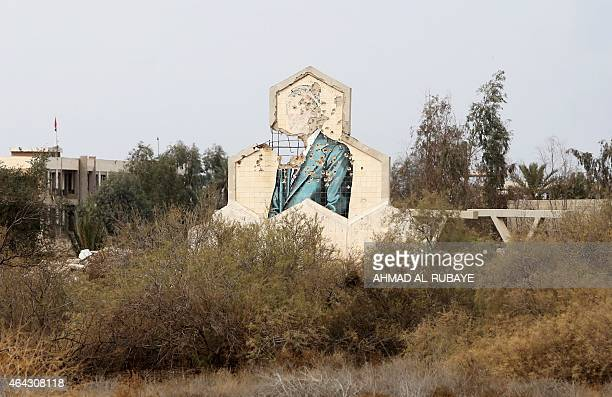 A general view shows the bullet riddled mural of Iraqi former President Saddam Hussein on a building in the village of of Fadhiliyah which...