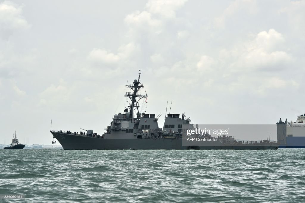 A general view shows the guided-missile destroyer USS John S. McCain with a hole on its left portside after a collision with oil tanker, outside Changi naval base in Singapore on August 21, 2017. Ten US sailors were missing and five injured early on August 21 after their destroyer collided with a tanker east of Singapore, the second accident involving an American warship in two months. /