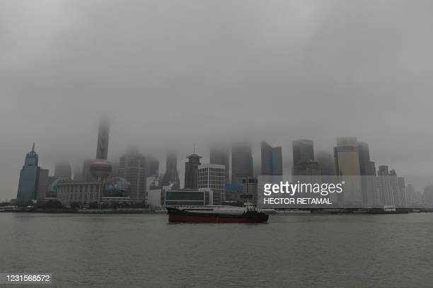 General view shows the Lujiazui financial district along the Huangpu river in Shanghai on March 7, 2021.