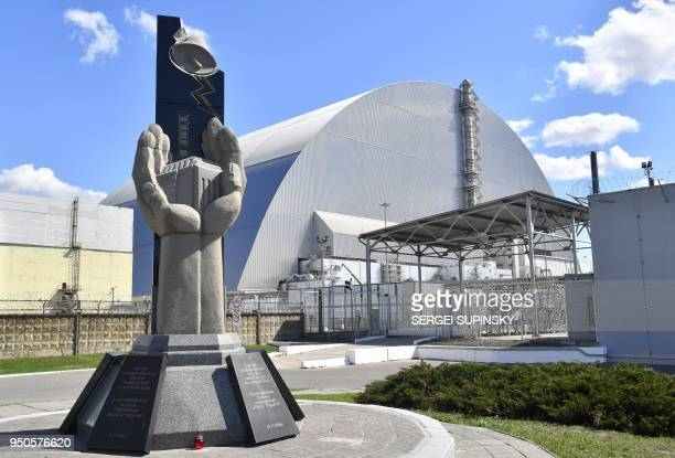 A general view shows the monument in memory of the victims of the Chernobyl nuclear disaster in front of Chernobyl's New 108 metres Safe Confinement...