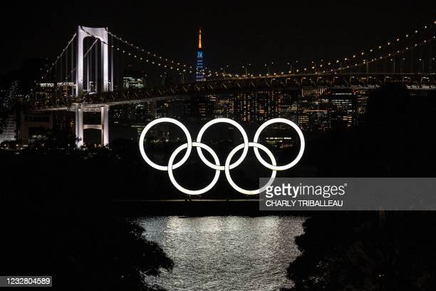 General view shows the Olympic rings lit up at dusk, with the Rainbow bridge and the Tokyo Tower in the background, on the Odaiba waterfront in Tokyo...
