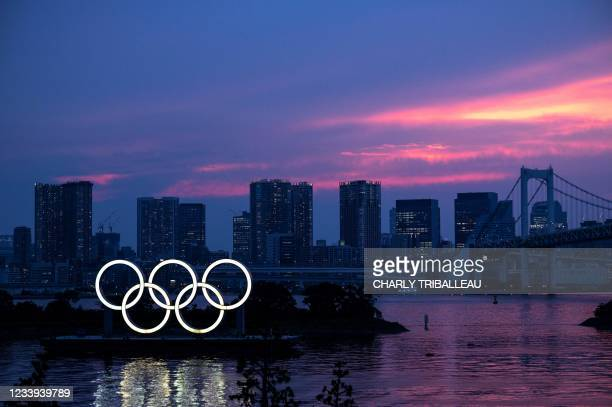 General view shows the Olympic rings lit up at dusk, with the Rainbow bridge in the background, on the Odaiba waterfront in Tokyo on July 12, 2021.