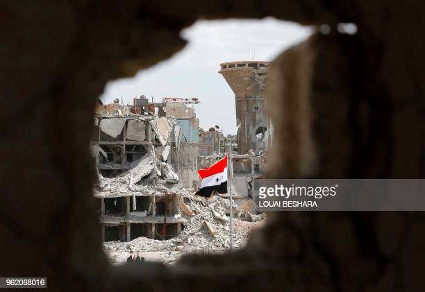 A general view shows the Syrian flag flying in a rubble strewn street during a flag raising ceremony at the entrance of the Hajar alAswad...
