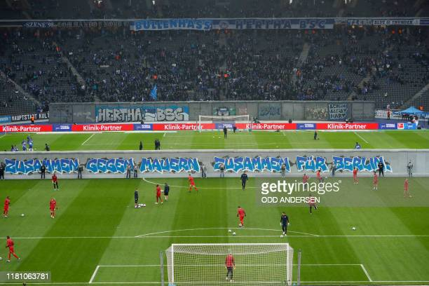 "General view shows the teams warming up on either side of a mock-up of the former Berlin Wall bearing the inscrition ""Together gainst Walls, together..."
