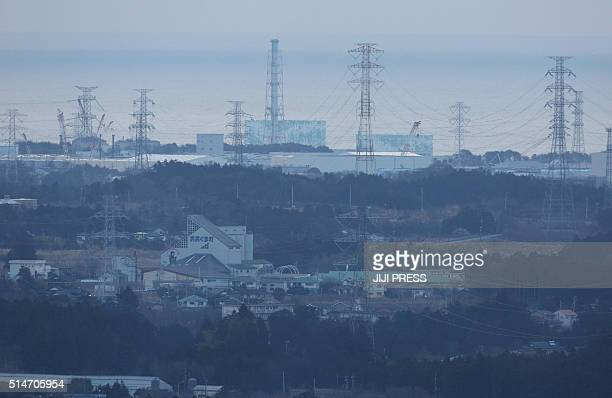 A general view shows the troubled Fukushima Daiichi nuclear power plant seen from Tomioka town in Fukushima prefecture on March 11 as people gather...