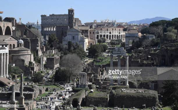 A general view shows tourists visiting the Roman Forum with the ancient Colosseum in the background on March 11 2017 in Rome / AFP PHOTO / Tiziana...