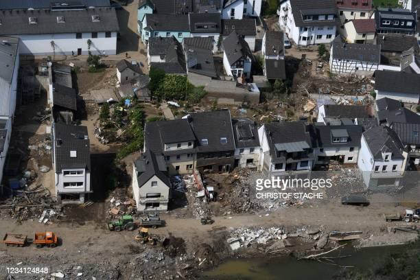 General view shows trucks removing debris in front of destroyed houses in the municipality of Mayschoss in the district of Ahrweiler, western...