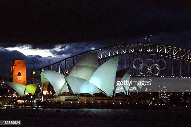 general view taken 11 September 2000 of the Olympics rings on the Harbour bridge behind the Opera House in Sydney four days before the opening...