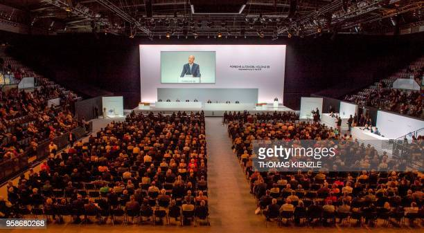 General view taken as Hans Dieter Poetsch CEO of Porsche Automobil Holding SE appears on a screen as he speaks during the company's annual...