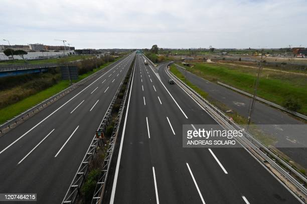 General view taken from a bridge shows a few cars driving through a deserted highway leading Rome's Fiumicino international airport to Rome on March...