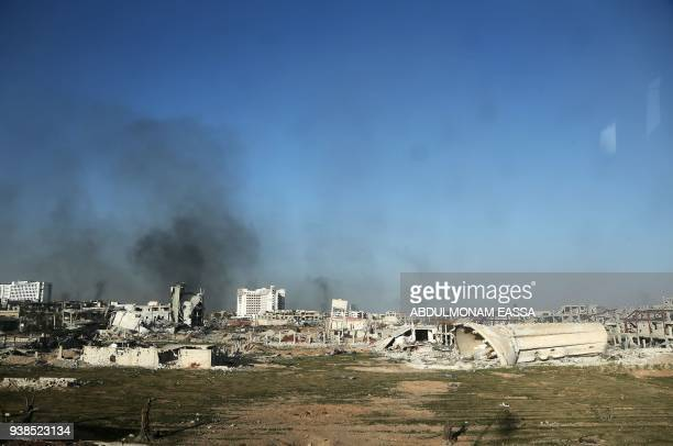 TOPSHOT A general view taken from a bus in a convoy transporting Syrian civilians and rebel fighters shows smoke rising from destroyed buildings in...