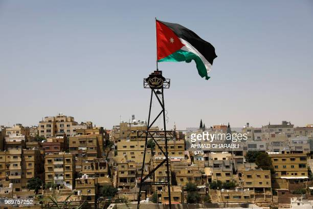 General view taken from Jabal al-Qala district shows a Jordanian flag fluttering above the Jordanian capital Amman on June 8, 2018. - Jordan's...