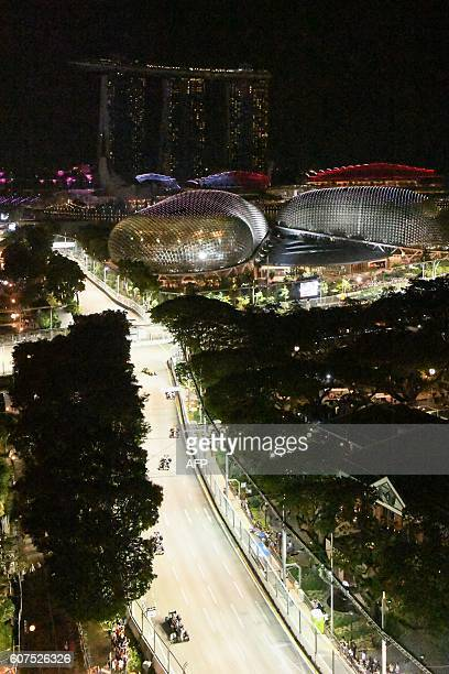 TOPSHOT A general view taken from Swissotel The Stamford shows the drivers drive under the lit circuit for the Formula One Singapore Grand Prix night...