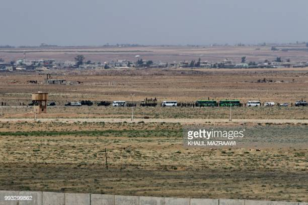 A general view taken from the Jordanian Mafraq governate on July 7 shows military vehicle and busses across the border in Syria a day after Syrian...