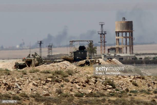 A general view taken from the Jordanian Mafraq governate on July 7 shows military vehicle across the border in Syria a day after Syrian government...