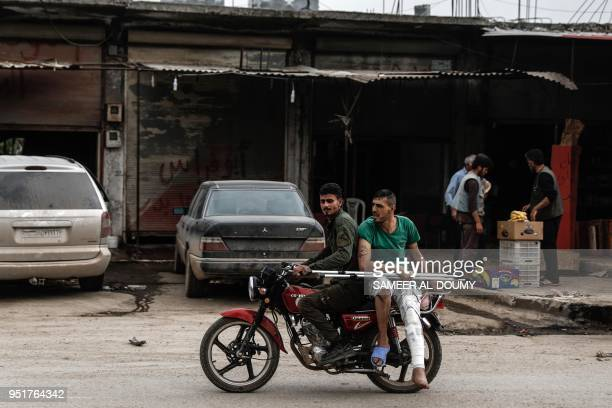 TOPSHOT A general view taken on April 26 shows an injured man riding on the back of his friend's motorbike in the northern Syrian enclave of Afrin...