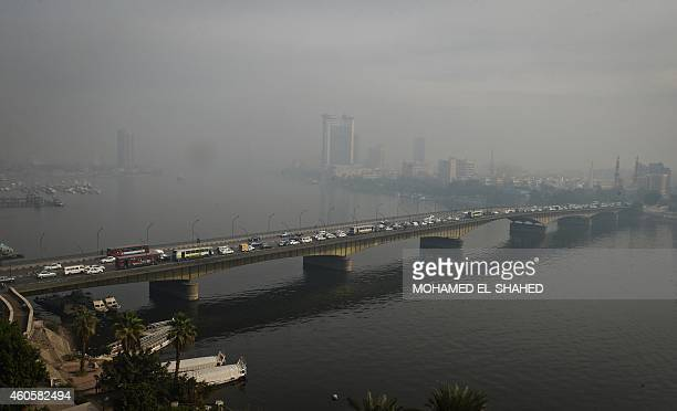 A general view taken on December 17 2014 shows pollution hovering over Egypt's Nile river and the University bridge in Cairo AFP PHOTO / MOHAMED...